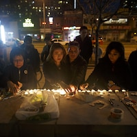 Des Torontois déposent des chandelles sur un palissade commémorative rendant hommage aux victimes de l'attaque au camion-bélier.