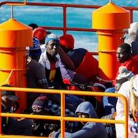 Des migrants africains sont assis sur le pont du bateau.