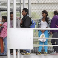 Cinq migrants voulant demander l'asile aux États-Unis attentent sur un pont du côté mexicain de la frontière.