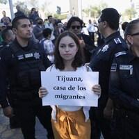 La femme tient son affiche dans une rue, elle est entourée de policiers.