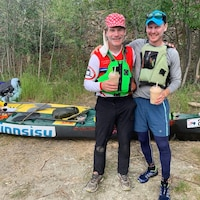 Mike Vincent (à gauche) et Ivan English sont debout un verre à la main devant leur canoë.