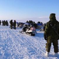 Un militaire avec son arme sur le dos regarde ses collègues et l'étendue de l'Arctique au loin.