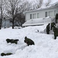 Des militaires déblaient l'entrée d'une résidence à Terre-Neuve.