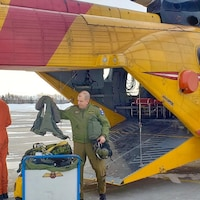 Trois militaires transportent du matériel à l'intérieur d'un hélicoptère canadien.