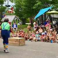 Des enfants assis sur le sol devant une équipe de clowns professionnels.