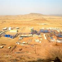 Des installations, avec des bâtiments et des véhicules, situées au milieu d'un désert.