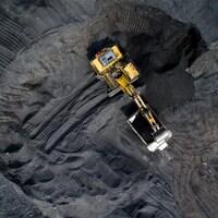 Une pelle mécanique déverse du charbon dans une benne, dans une mine à ciel ouvert.