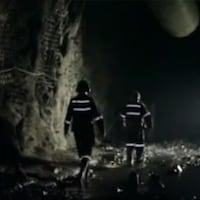 Deux travailleurs marchent dans une galerie de mine.