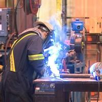 Un travailleur soude une pièce de métal