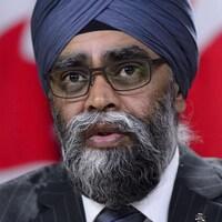 Harjit Sajjan en veston-caravate porte un turban sur la tête. deux fois le mot .