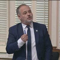 Le ministre Jonatan Julien est debout à l'Assemblée nationale et il répond à une question.