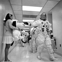 Le commandant de la mission Apollo 10, Thomas Stafford, dans son habit de cosmonaute marche dans un long corridor.