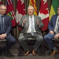 Les trois premiers ministres sont assis sur des chaises l'un à côté de l'autre devant des drapeaux canadiens et de leurs provinces respectives.