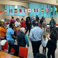 Des dizaines de personnes de différentes nationalités dansent en cercle dans une salle décorée de plusieurs drapeaux.
