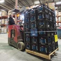 Un bénévole manoeuvre un engin de manutention transportant des caisses de lait dans un entrepôt de l'organisme Moisson Montréal.