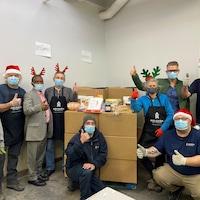Des bénévoles de Moisson Outaouais posent devant les paniers de Noël.
