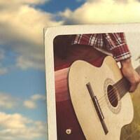 Carte postale illustrant l'épisode 7 de la série audio Mon Amérique. Une personne porte une guitare dans un champ.