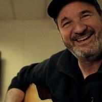 Paul Piché assis tient une guitare