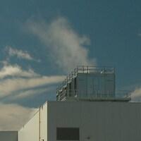 Des tours de refroidissement sur le toit d'un bâtiment industriel.