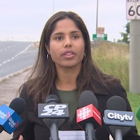 Monica Hudon en point de presse sur le bord de la route.