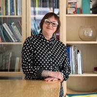 Une photo de Monique Savoie devant une grande bibliothèque en bois.