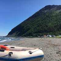 Un bateau pneumatique repose sur une plage. On voit que la plage est bordée par une grande montagne et quelques maisons. Des vagues viennent toucher la rive.