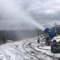 Un canon fabrique la neige sur une montagne. Le sol n'est pas encore totalement recouvert.