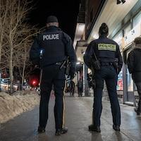 Des policiers sur le trottoir d'une rue commerciale d'un village de montagne, l'hiver.
