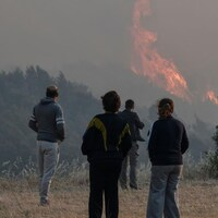 Des gens regardent au loin les flammes s'élever vers le ciel.