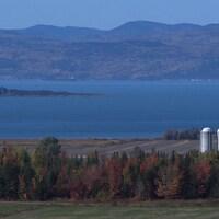 Une vue du fleuve Saint-Laurent, avec des silos de ferme en avant-plan et les montagnes de Charlevoix en arrière-plan.