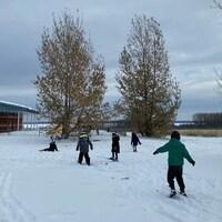 Des enfants, à skis, dans la neige.