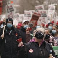 Des manifestants portant un couvre-visage et arborant des pancartes se tiennent à l'extérieur : à l'avant-plan, une femme agite une clochette en regardant vers le ciel.