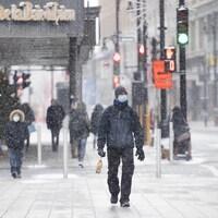 Des passants dans le centre-ville de Montréal sous une neige fine.
