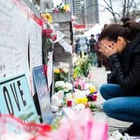 Une femme est accroupie devant des messages et des fleurs.