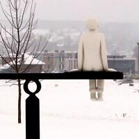 Un monument représentant un enfant et un oiseau regardant au loin.