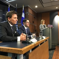 Pierre Moreau et Éric Martel assis devant une table lors d'une conférence de presse.