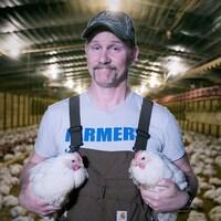 Morgan Spurlock tient deux poulets dans un poulailler.
