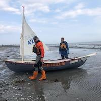 Justin Roy et Nicolas Roy se promènent autour de leur bateau à voile qui est accosté sur la plage.