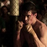 Un personnage du film Mortal Kombat dans un ring de boxe, les mains gantées et le visage ensanglanté.