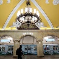 Une rame de métro arrive dans la station Komsomolskaya, la plus photogénique de Moscou, avec ses colonnes de marbre, ses fresques au plafond et ses moulures blanches sur fond jaune.