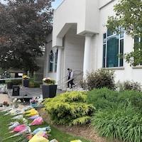 Des bouquets sont sur le sol des deux côté de l'entrée principale.
