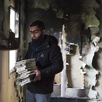 Une homme ramasse les débris dans une mosquée ravagée par un feu criminel en novembre 2015, à Peterborough.