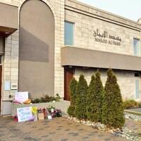 La devanture de la mosquée où des fleurs et des messages se trouvent.