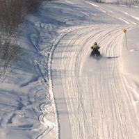 Un motoneigiste dans un sentier balisé de la Gaspésie