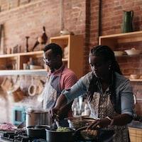 Un couple cuisine dans un espace qui semble assez grand. Ils s'affairent devant des casseroles et une plaque de cuisson.