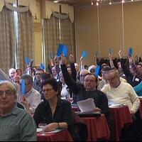 Des représentants de municipalité tendent un bulletin bleu en signe d'approbation.