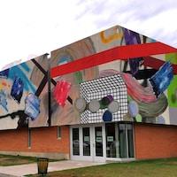 La murale très colorée est à cheval sur la majeure partie de deux murs qui forment un angle.