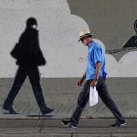 Un piéton marche devant la murale représentant la silhouette d'un homme masqué.