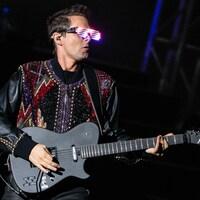 Le chanteur de Muse, Matthew Bellamy , est vêtu d'une veste de cuir à paillettes et porte des lunettes composées de lumières. Il joue de la guitare.
