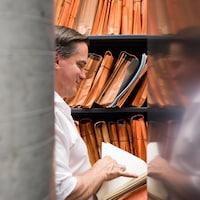 Le musicothécaire de l'OSM, Michel Léonard, feuillette une partition alors que son visage est reflété sur une étagère en métal.